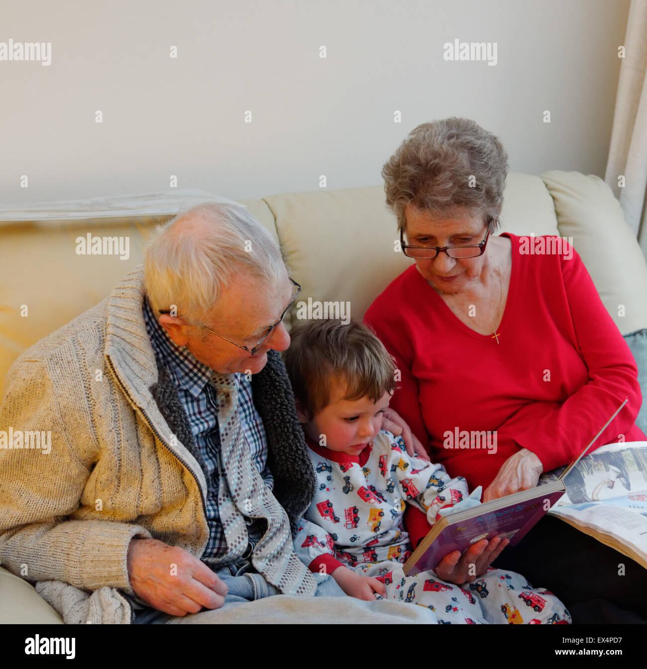 Un niño pequeño (3 años) en pijama tiene un cuento con sus abuelos Imagen De Stock