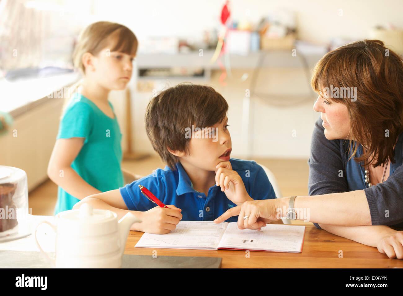 Madre e hijo haciendo los deberes en la Mesa de la cocina, hija en segundo plano. Foto de stock