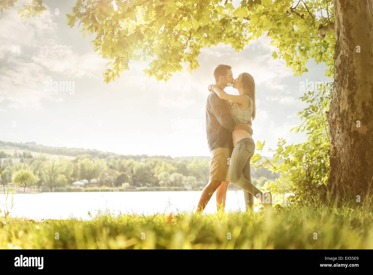 Pareja en el amor sobre el lago, bajo los árboles, besos Imagen De Stock