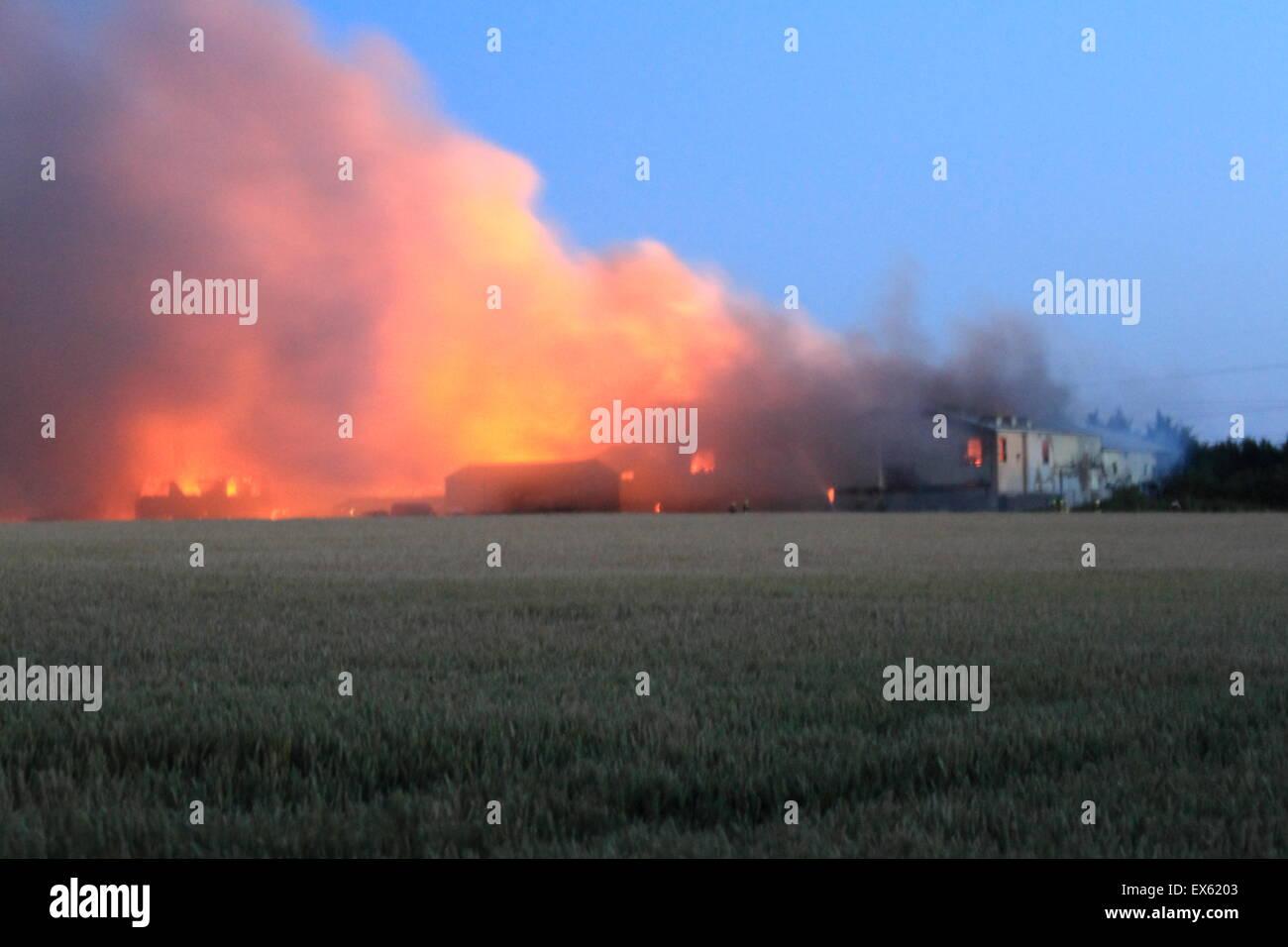 Rainham, Londres, Reino Unido. Martes, 7 de julio de 2015. Más de 80 bomberos abordar blaze en un astillero de palets en Rainham. 12 bomberos de tres bomberos fueron llamados a la escena alrededor de las 8:00pm el martes por la noche. Kent y Essex, bomberos y servicios de rescate fueron llamados para ayudar a afrontar la Brigada de Bomberos de Londres Blaze. Una pila de palets y un número de edificios están implicados en el incendio. Formulario de humo el incendio podría ser visto por millas alrededor de vientos atizado las llamas. No hay informes de lesiones y la causa de la llamarada no se conoce todavía. Foto de stock