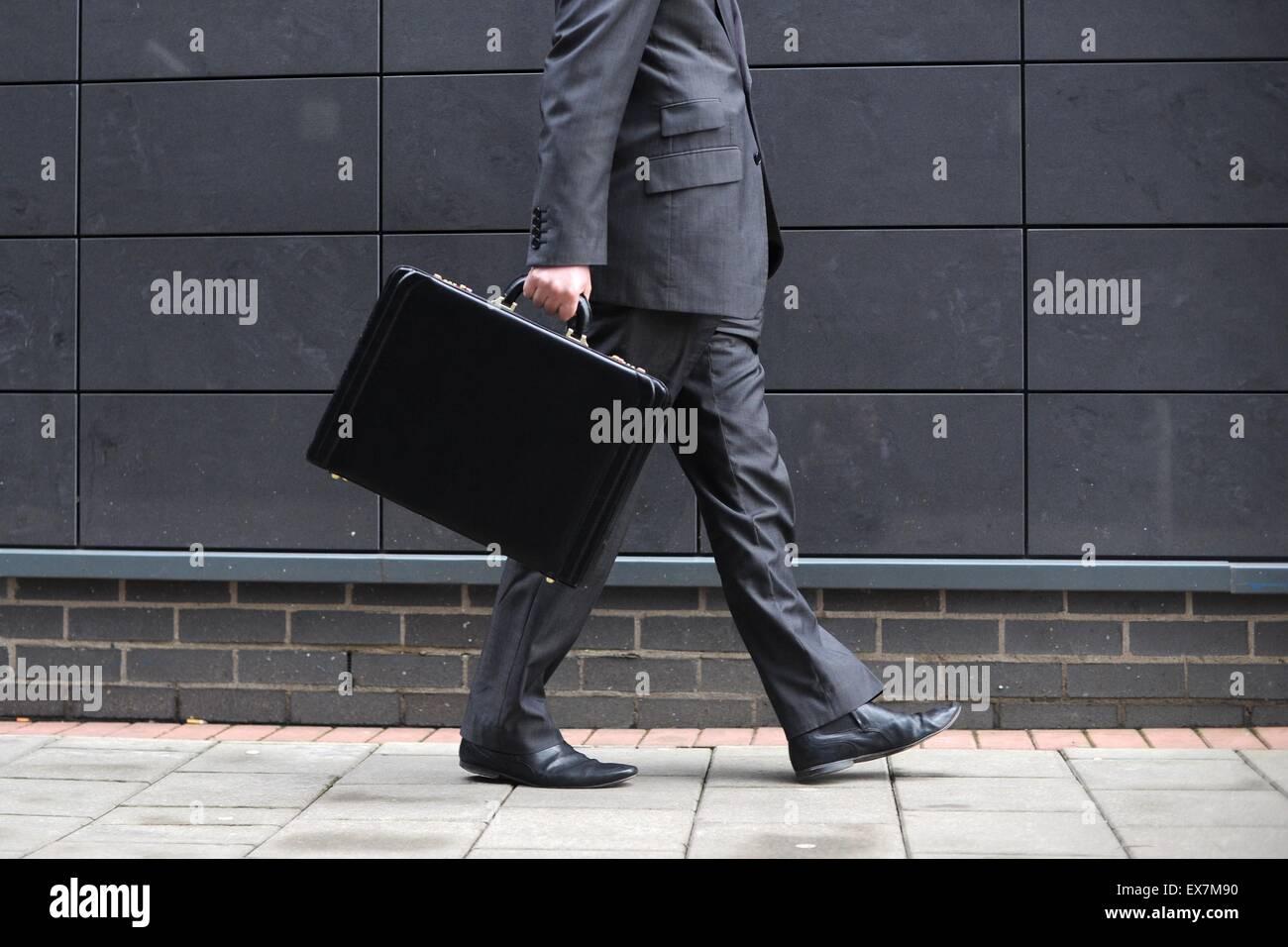 Un hombre de negocios lleva un maletín en el camino al trabajo en una oficina. Imagen De Stock