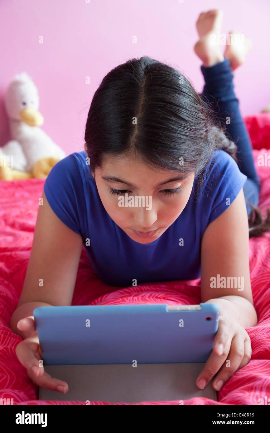 Adolescente llying en su cama y mirando su tableta digital Imagen De Stock