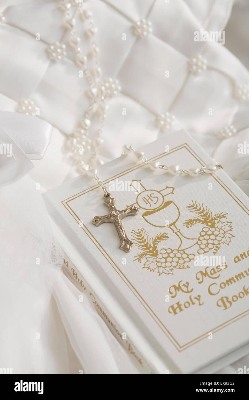 Libro de primera comunión, rosario con cruz de plata, blanco vestimenta religiosa Imagen De Stock