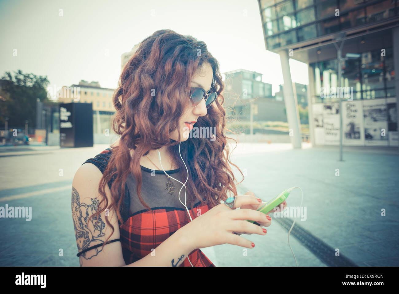 Hermosa joven hipster mujer con cabello rizado rojo escuchando música en la ciudad Imagen De Stock