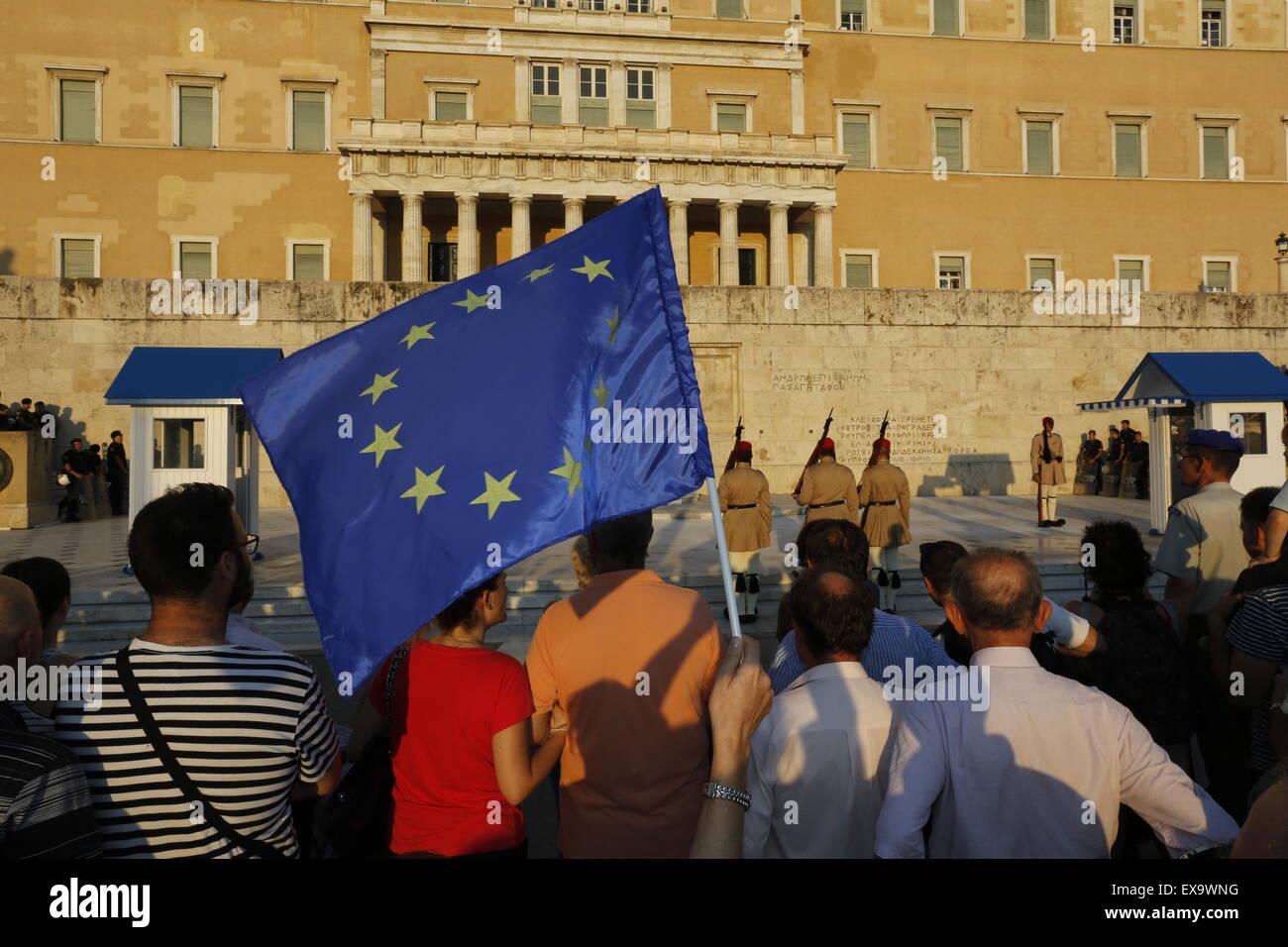 Atenas, Grecia. El 9 de julio de 2015. Un manifestante lleva una bandera europea, mientras los evzones (guardia Foto de stock