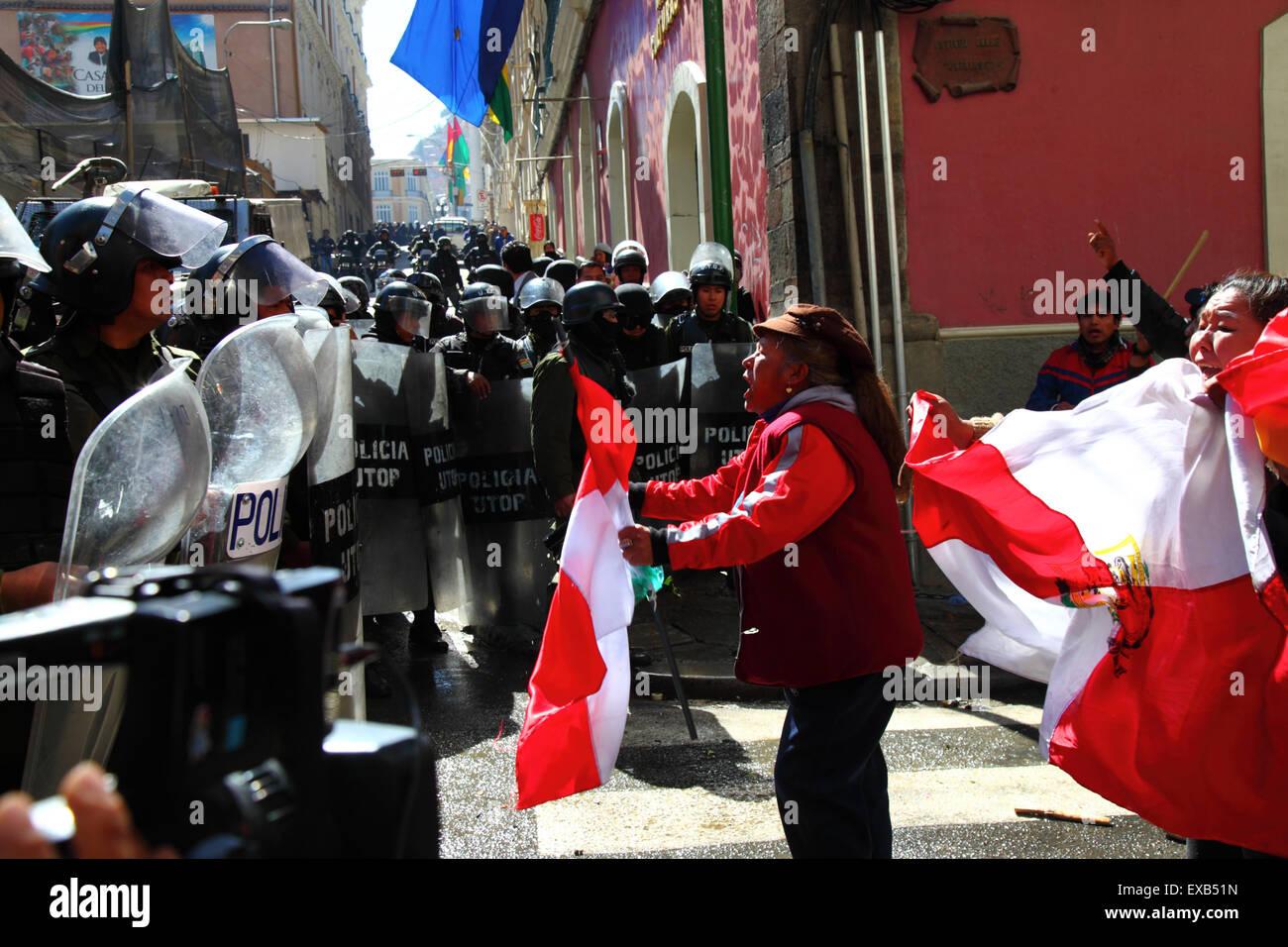 La Paz, Bolivia, 10 de julio de 2015. Un manifestante desde el área de Potosí se enfrenta a la policía antidisturbios durante una protesta por el Comité Cívico de Potosí y partidarios. Ellos están en La Paz para exigir que el gobierno mantiene las promesas hechas a la región en el pasado, que incluyen la construcción de una fábrica de cemento, hospitales, una planta hidroeléctrica y un aeropuerto internacional. La policía utilizó gas lacrimógeno para impedir a los manifestantes entrar en la Plaza Murillo (en el fondo, donde el Palacio Presidencial y el Congreso los edificios son) Credit: James Brunker/Alamy Live News Foto de stock
