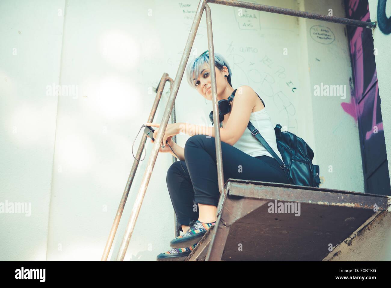 Hermosa joven de cabello azul corto hipster Mujer con auriculares de música en la ciudad Imagen De Stock