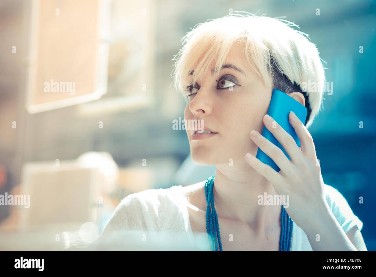 Hermosa joven rubia de cabello corto hipster mujer utilizando smart phone en el cafe Imagen De Stock
