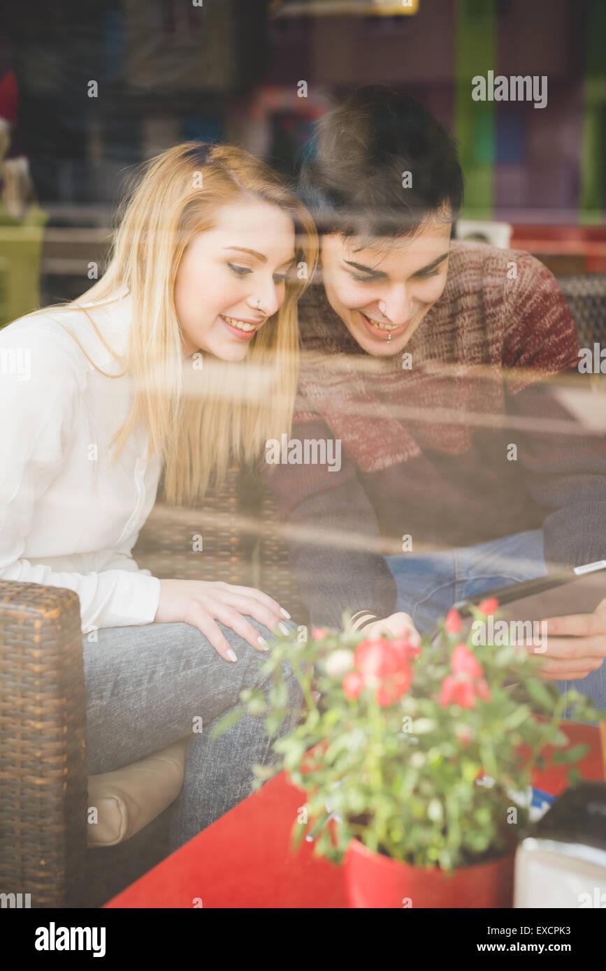 Los amantes de la Pareja hermosa joven sentado en la barra utilizando tableta inalámbrica conectada online Imagen De Stock