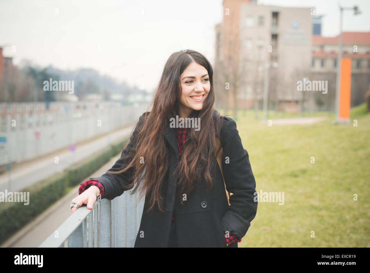Hermosa joven modelo cabello largo mujer viviendo en la ciudad en la ciudad al aire libre en invierno Imagen De Stock