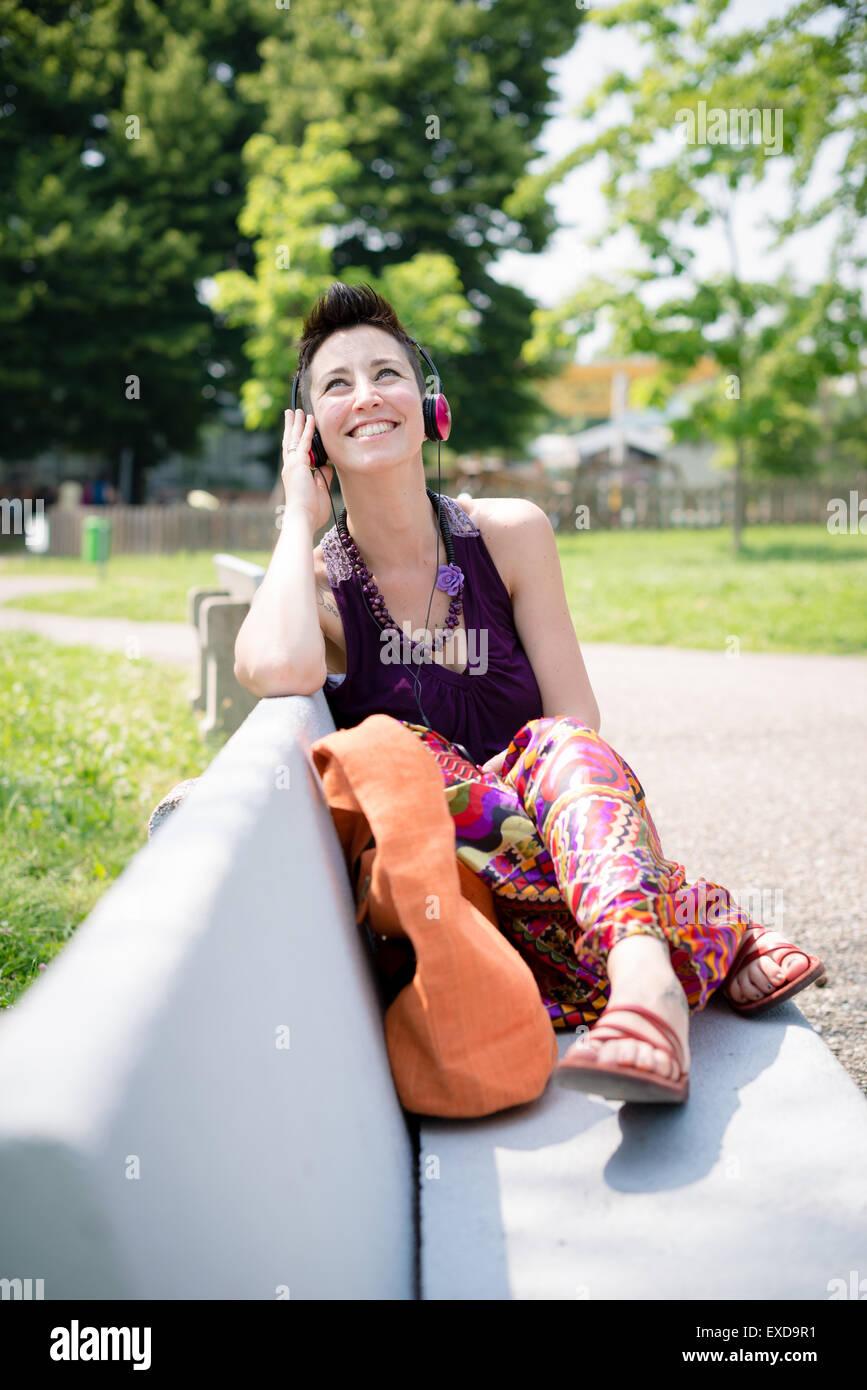 Hermosa hipster cabello corto mujer escuchando música en el parque de la ciudad Imagen De Stock