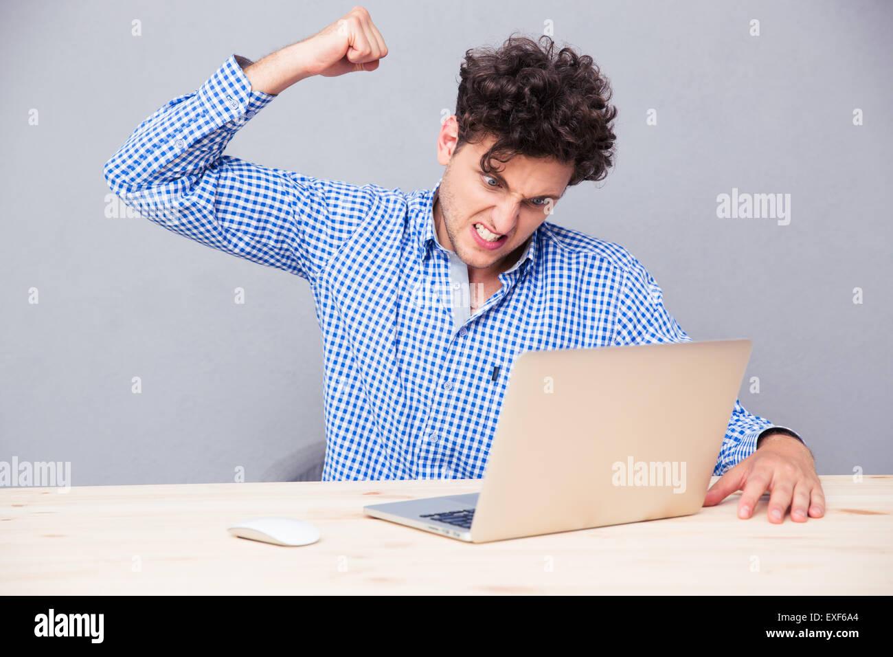El hombre enojado sentado a la mesa con el portátil sobre fondo gris Imagen De Stock