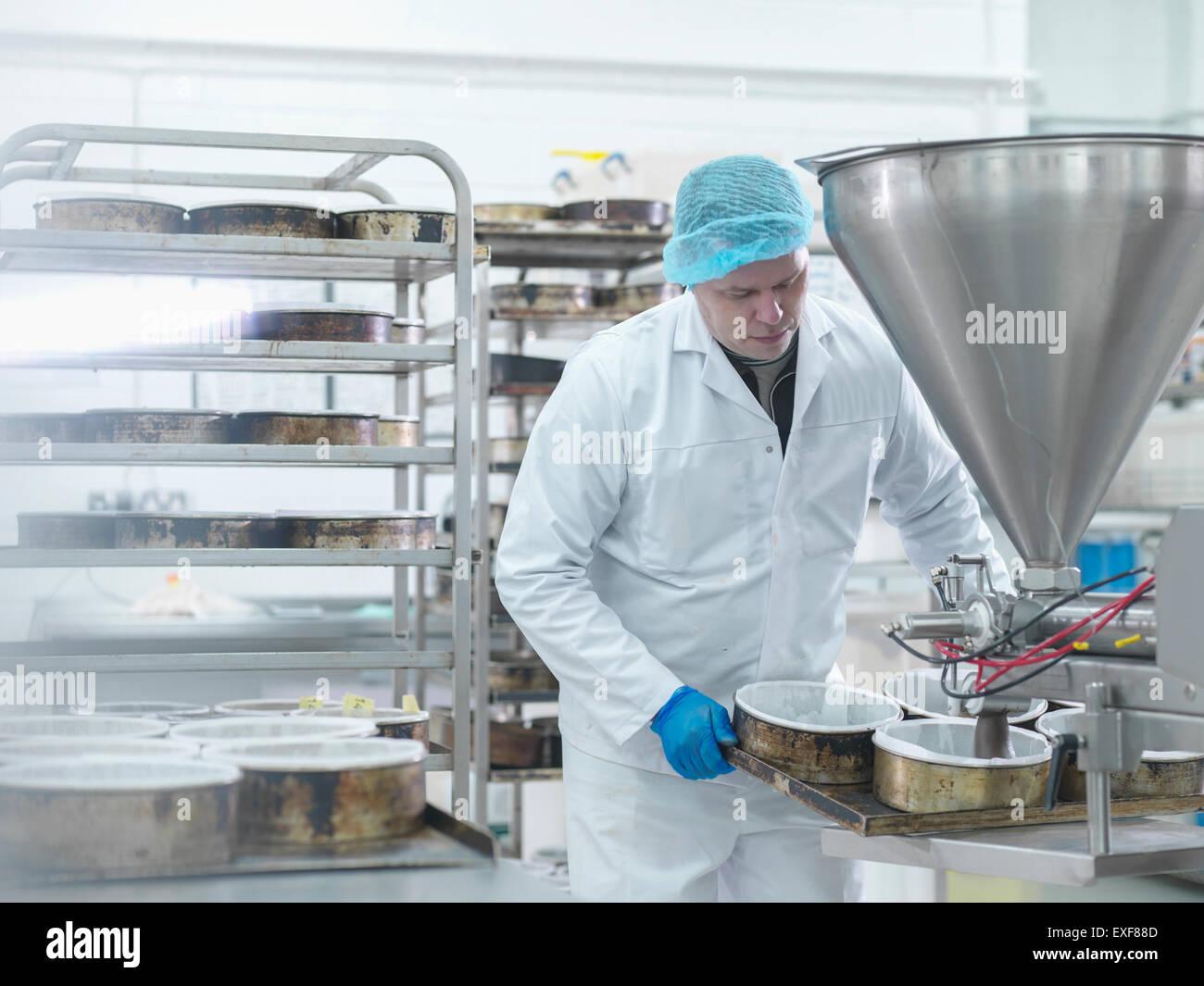 Trabajador masculino vertiendo cake mix en fábrica de pastel Imagen De Stock