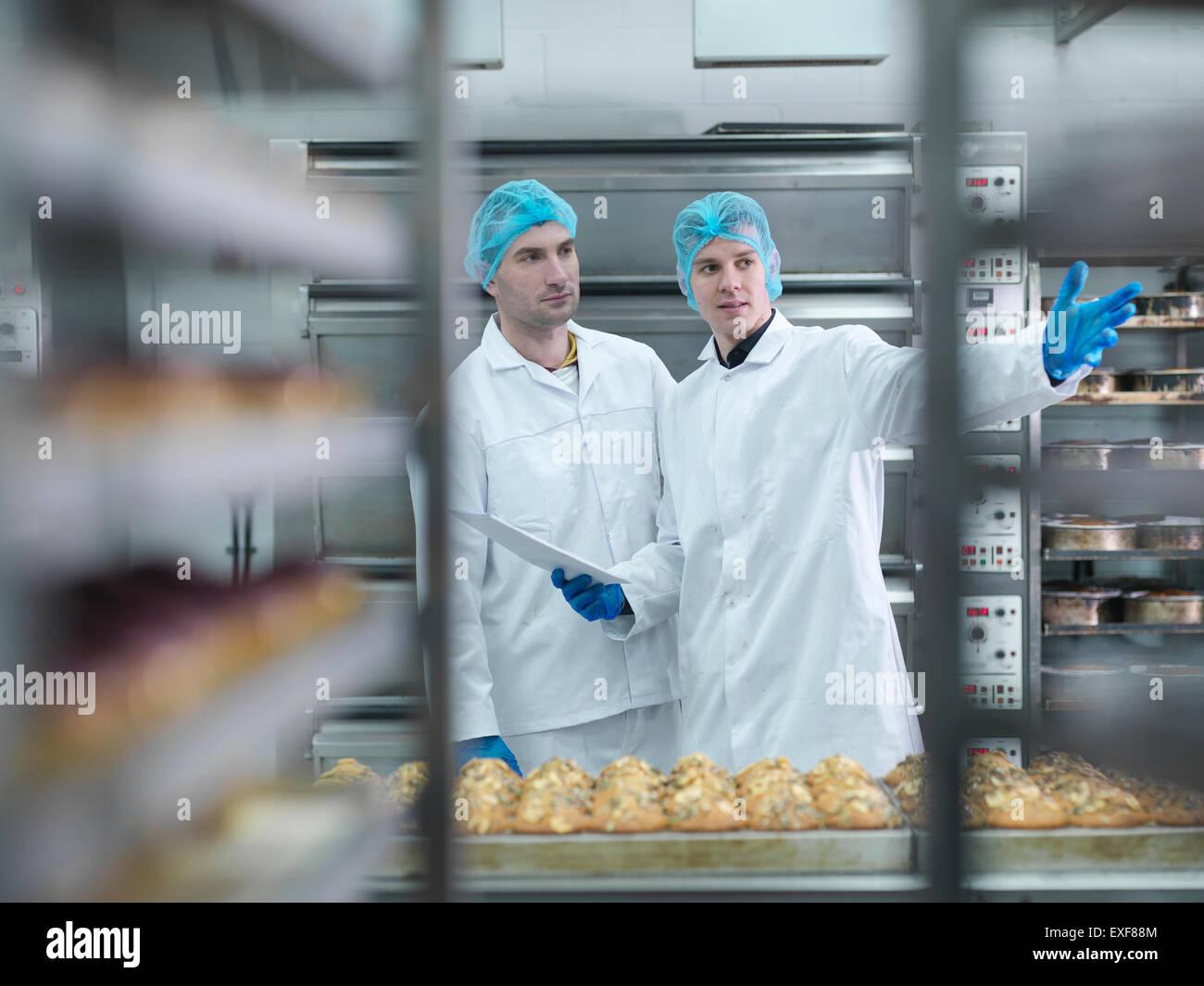 Los panaderos en reunión en fábrica de pastel Imagen De Stock