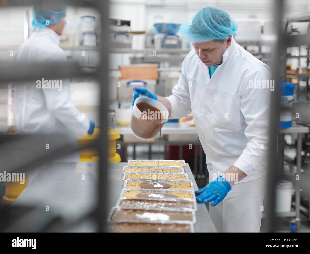 Trabajador masculino verter chocolate cake factory Imagen De Stock