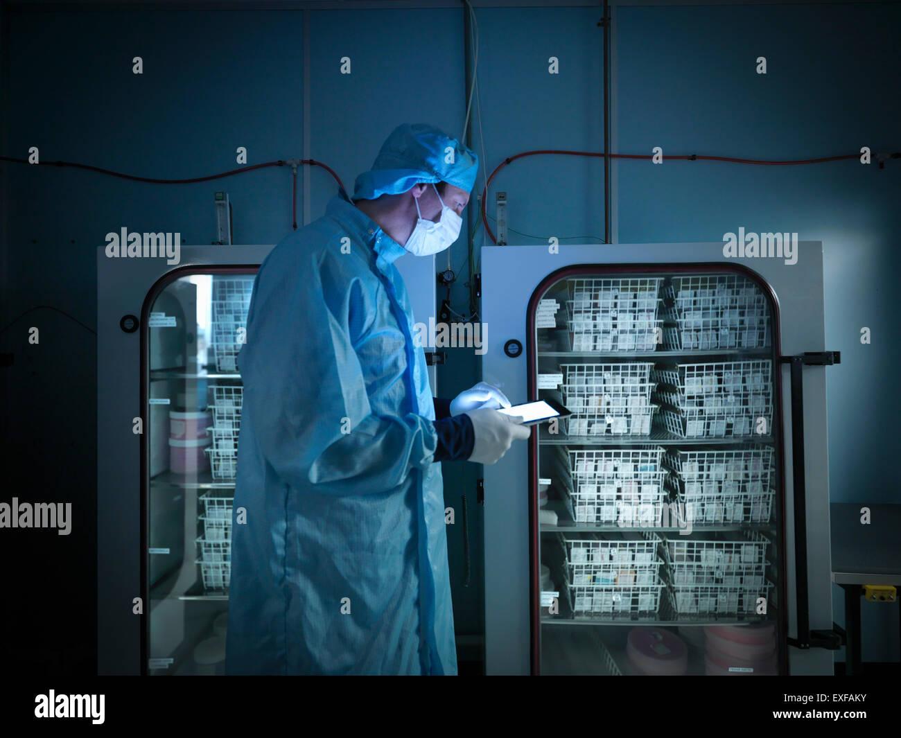 Trabajador utilizando tablet digital para comprobar componentes electrónicos archivados en atmósfera de Imagen De Stock