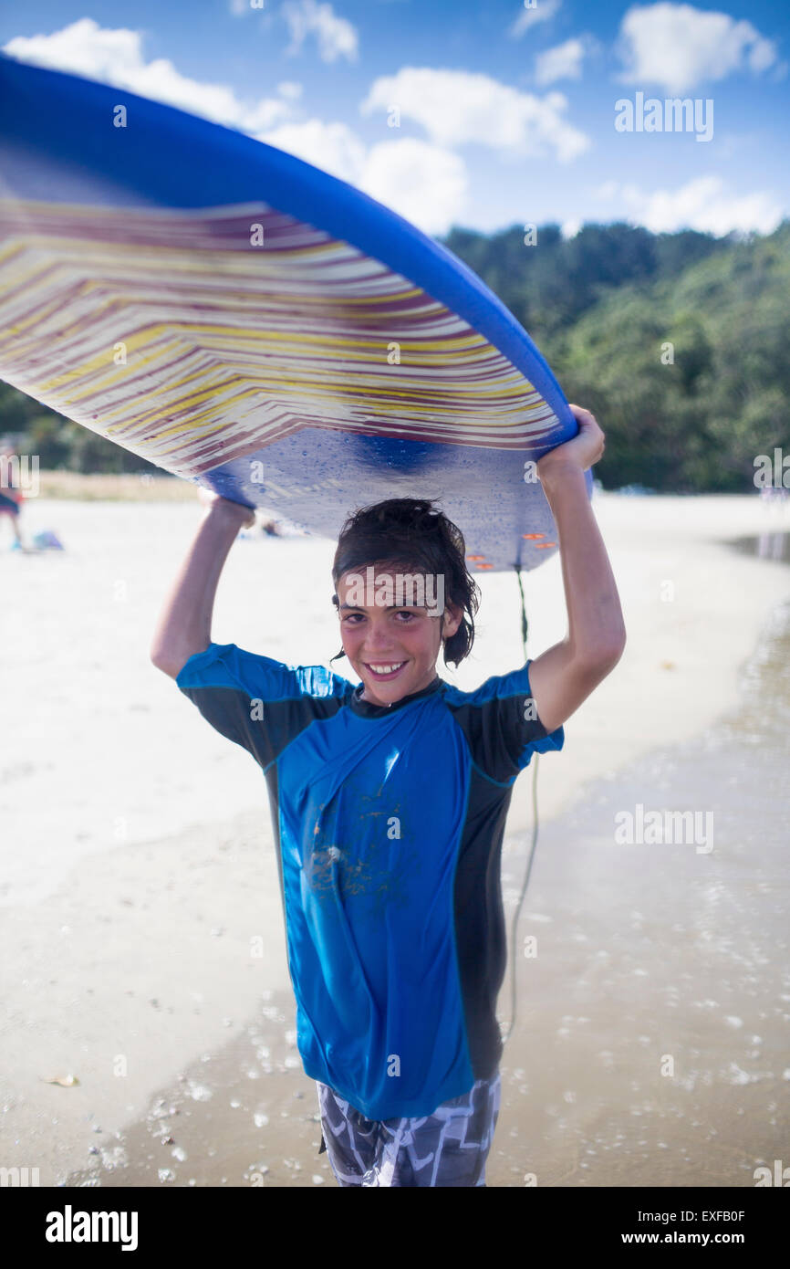 Chico surfer llevar tablas de surf Foto de stock