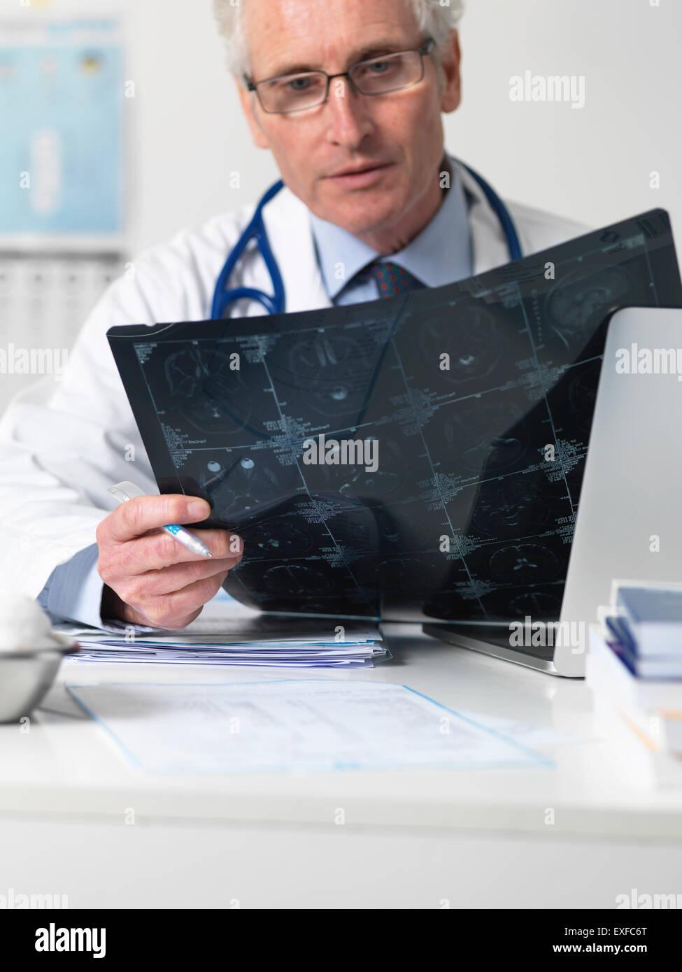 Doctor estudiando cinematografía hoja de la tomografía computarizada (TC) de diversas secciones a través Imagen De Stock