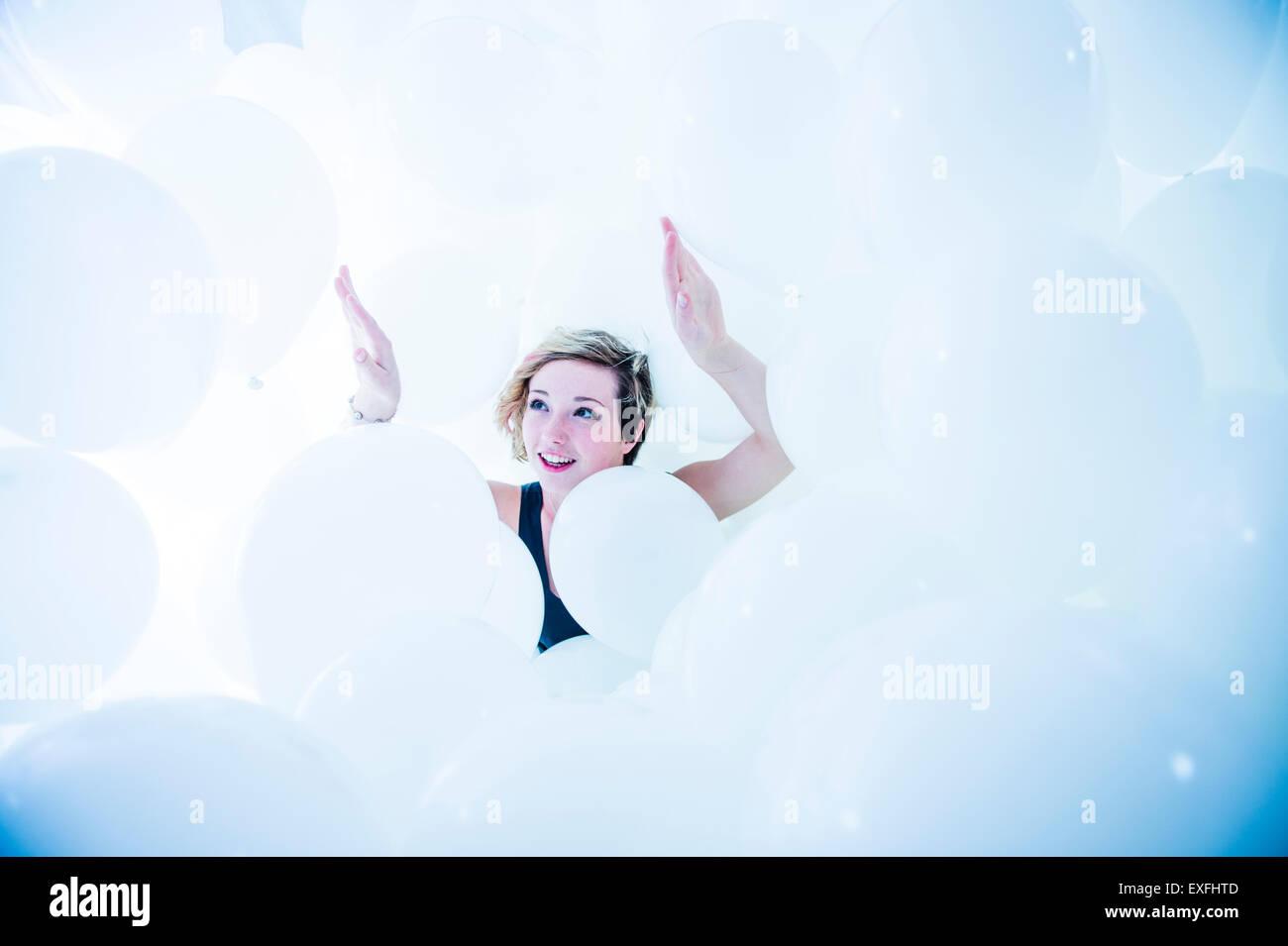 Globophobia: un feliz sonriente joven chica sola en una nube de cientos de globos blancos - tras superar su miedo Imagen De Stock