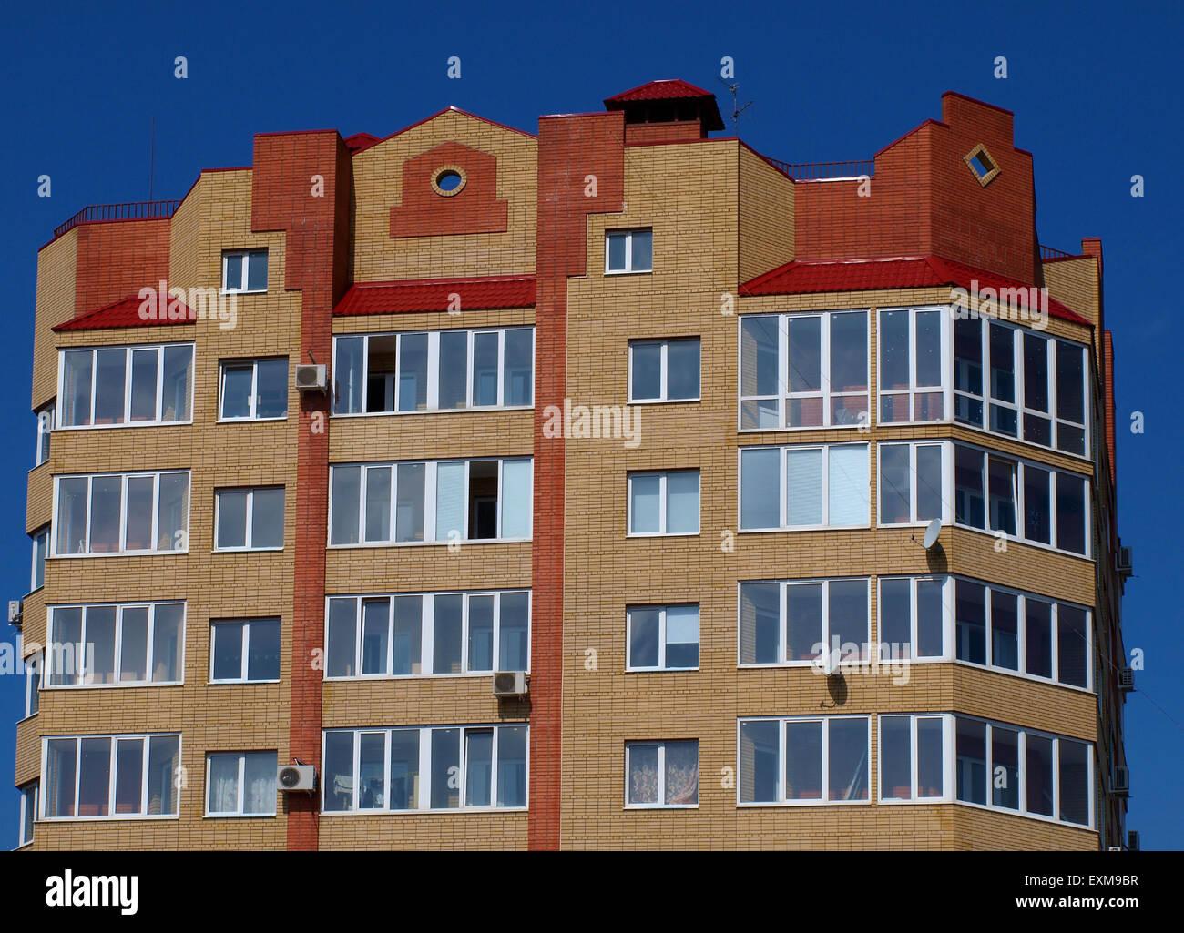 Los pisos superiores del edificio de varias plantas contra el azul del cielo sin nubes Imagen De Stock