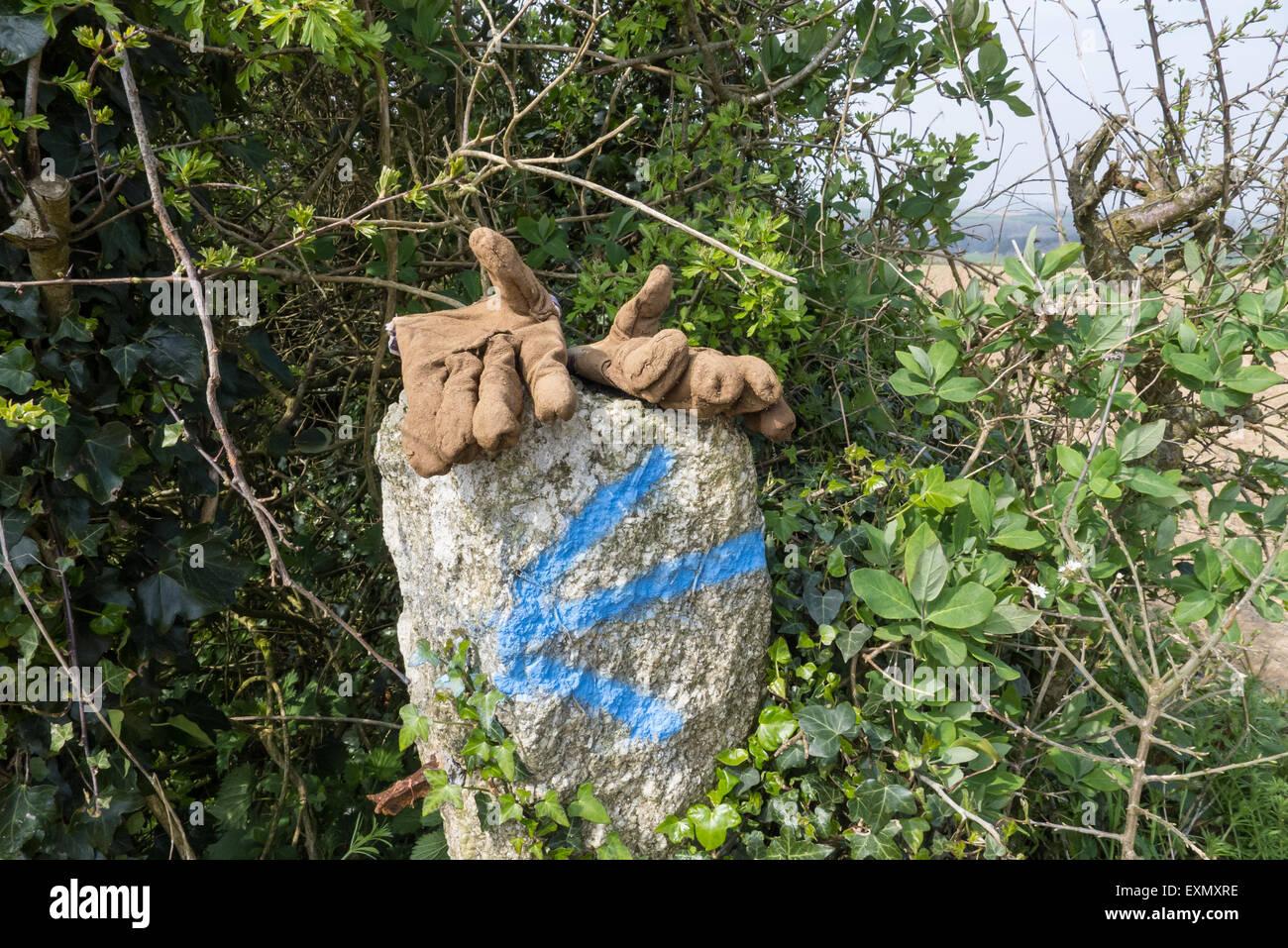 Cornwall, Inglaterra. Guantes de obrero en una piedra marcada con una flecha izquierda azul. Imagen De Stock