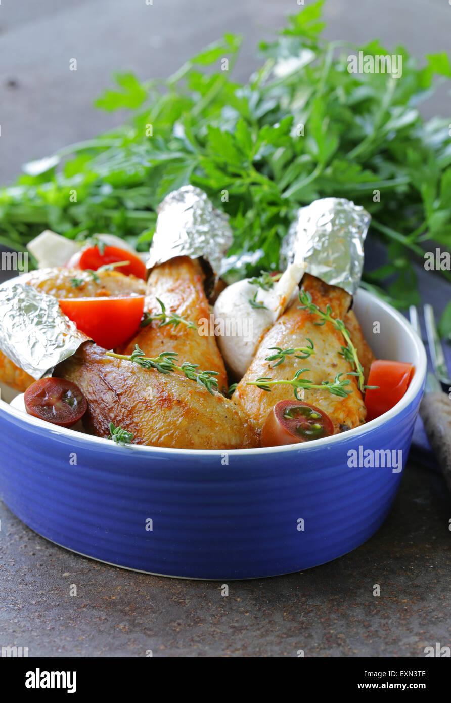Piernas de pollo frito con hierbas y especias, verduras para decorar Foto de stock
