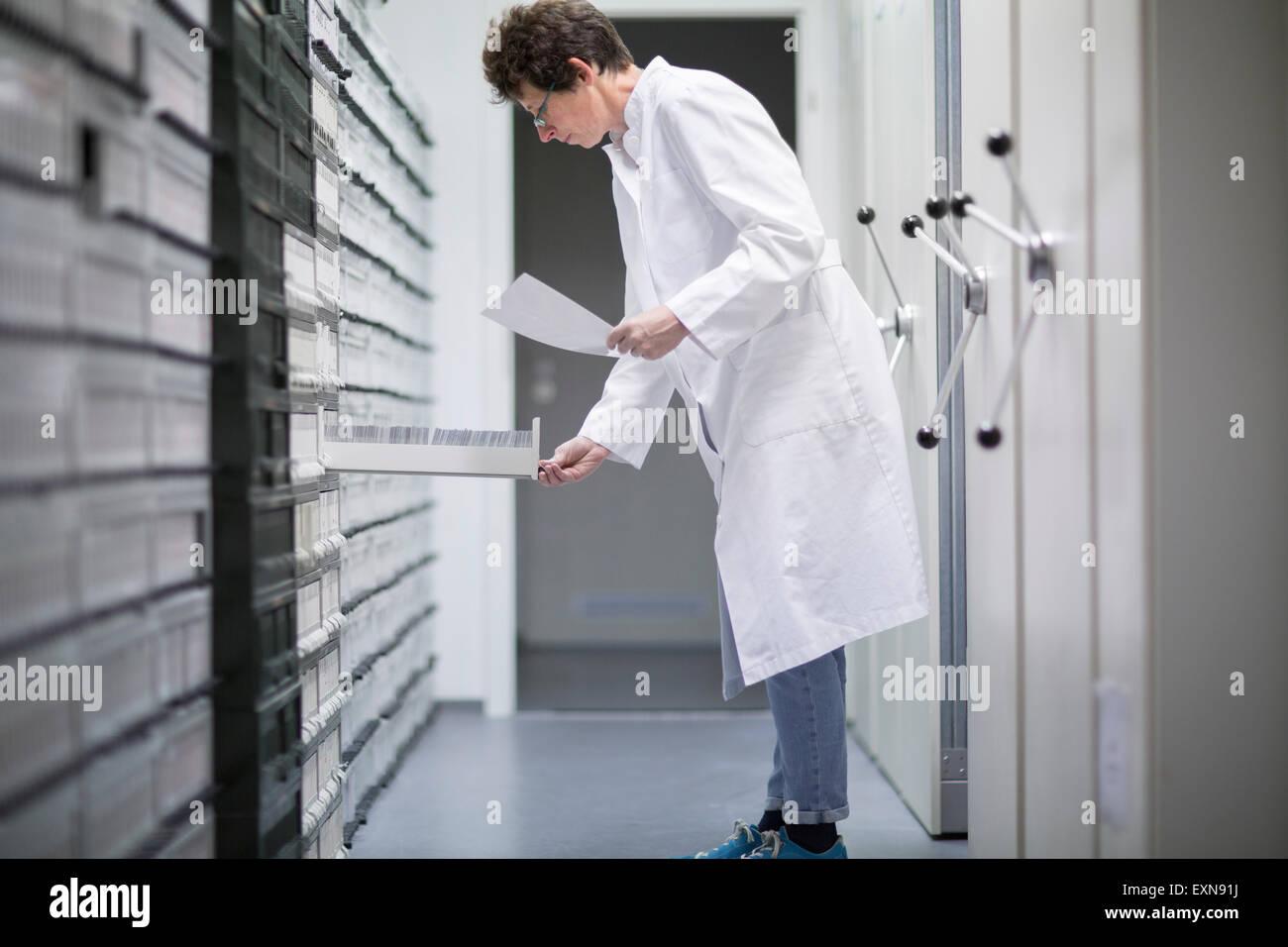 Auxiliar de laboratorio en el archivo de muestra de laboratorio clínico Imagen De Stock
