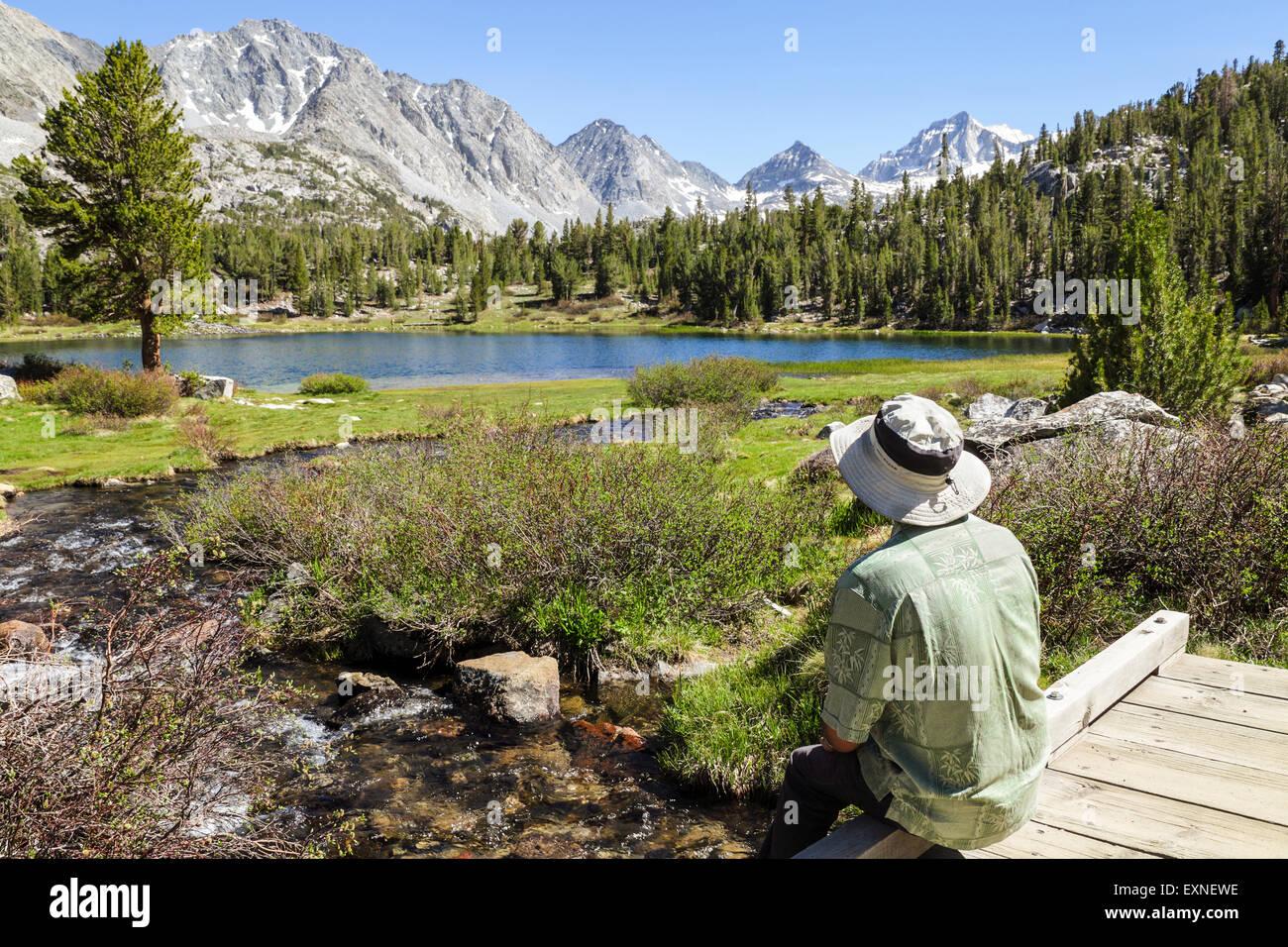 Descansando excursionista admira ver en pequeños lagos Valle en Rock Creek Canyon en la Sierra Oriental en Imagen De Stock