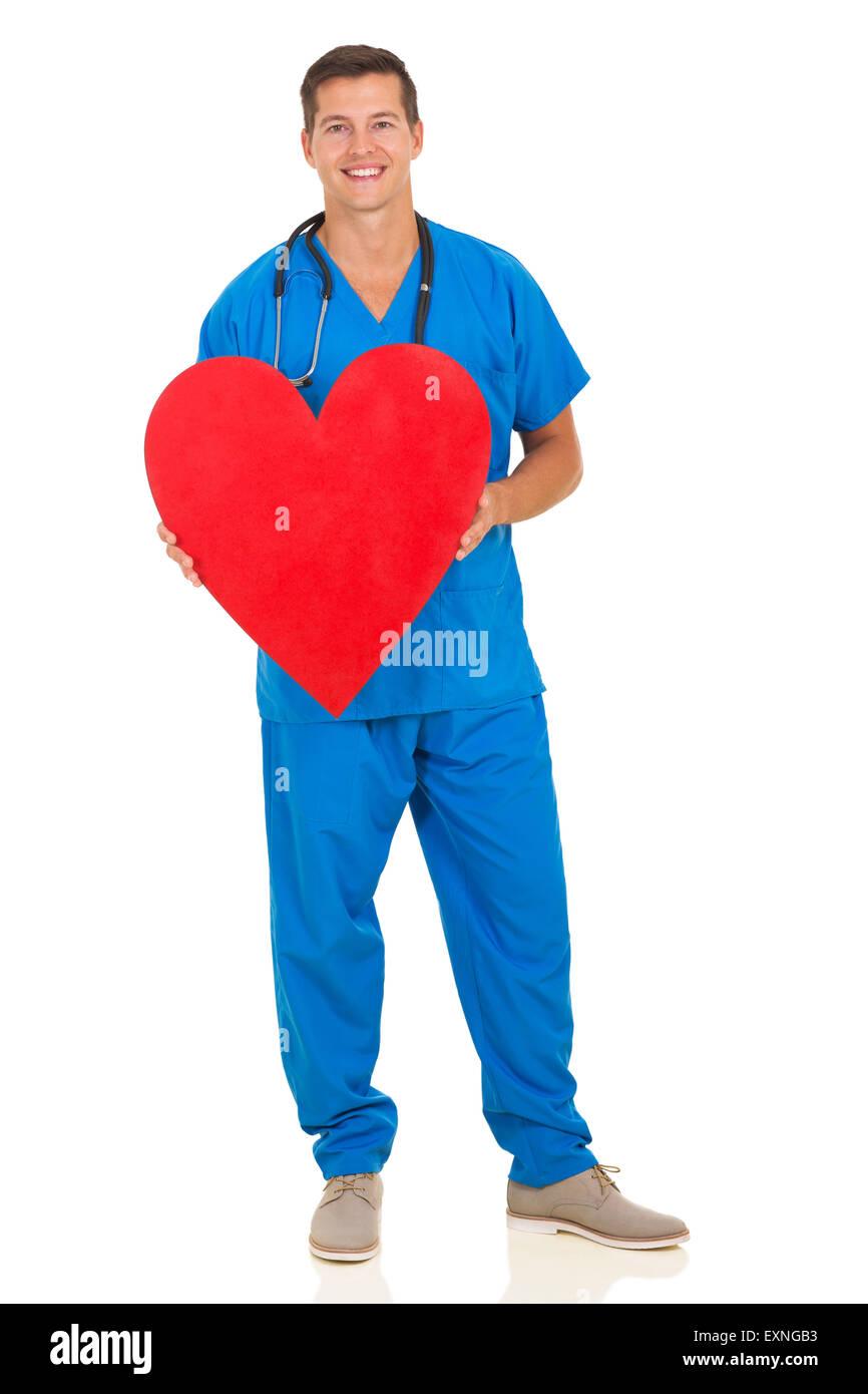 Atractiva joven médico celebración forma corazón sobre fondo blanco. Imagen De Stock