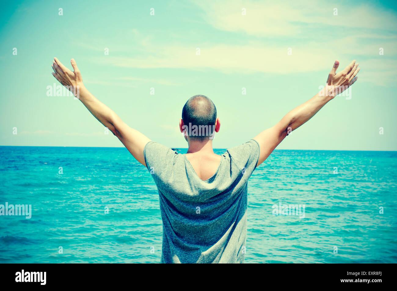 Primer plano de un joven hombre caucásico visto desde atrás con sus brazos en el aire delante del océano, sintiéndose Foto de stock