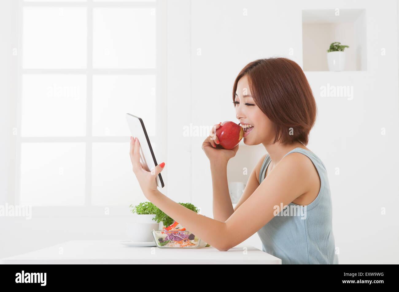 Mujer joven sosteniendo una manzana y la utilización del panel táctil, Imagen De Stock