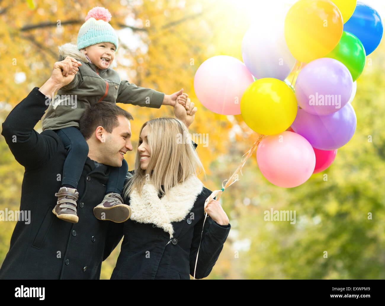 Familia feliz con el niño pequeño y el aire globos, paseo en el parque de otoño Imagen De Stock