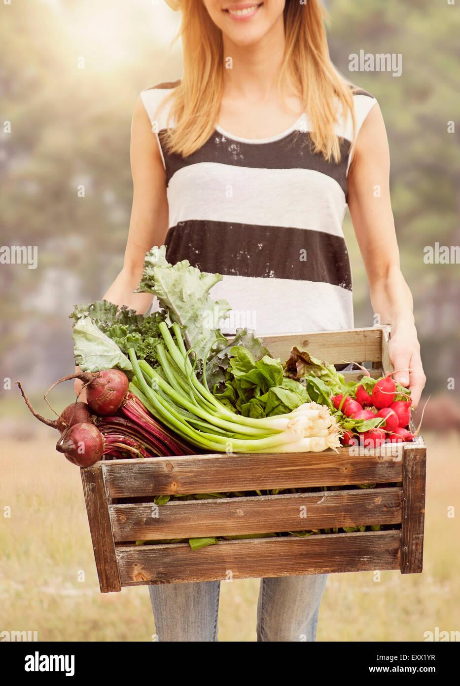 Mujer que llevaba verduras frescas en la casilla Imagen De Stock