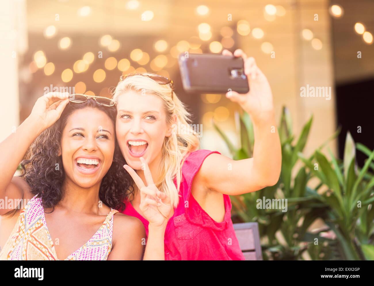 Amigas teniendo selfie con smart phone en cafe Imagen De Stock