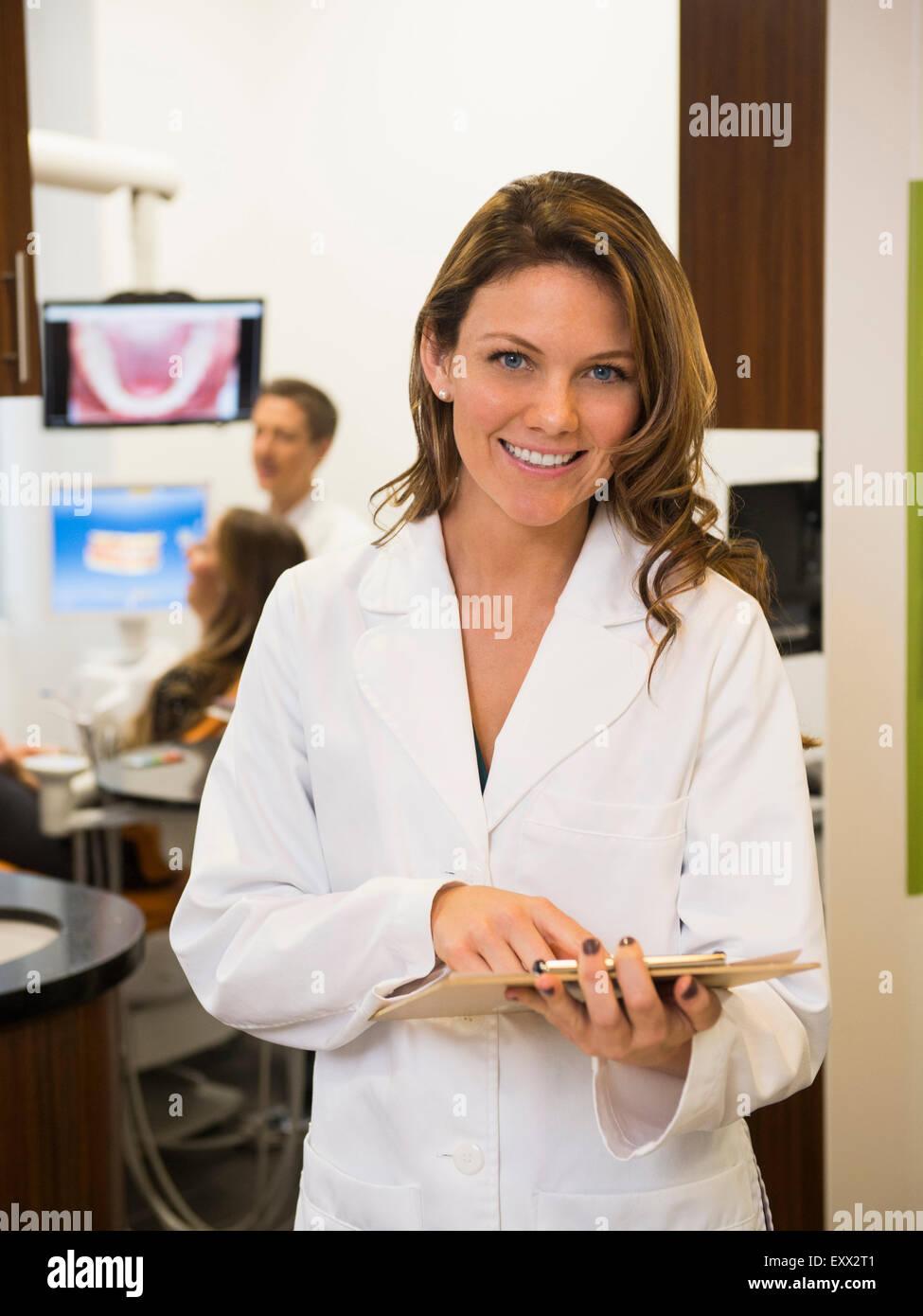 Retrato de dentista con su colega y paciente en segundo plano. Foto de stock