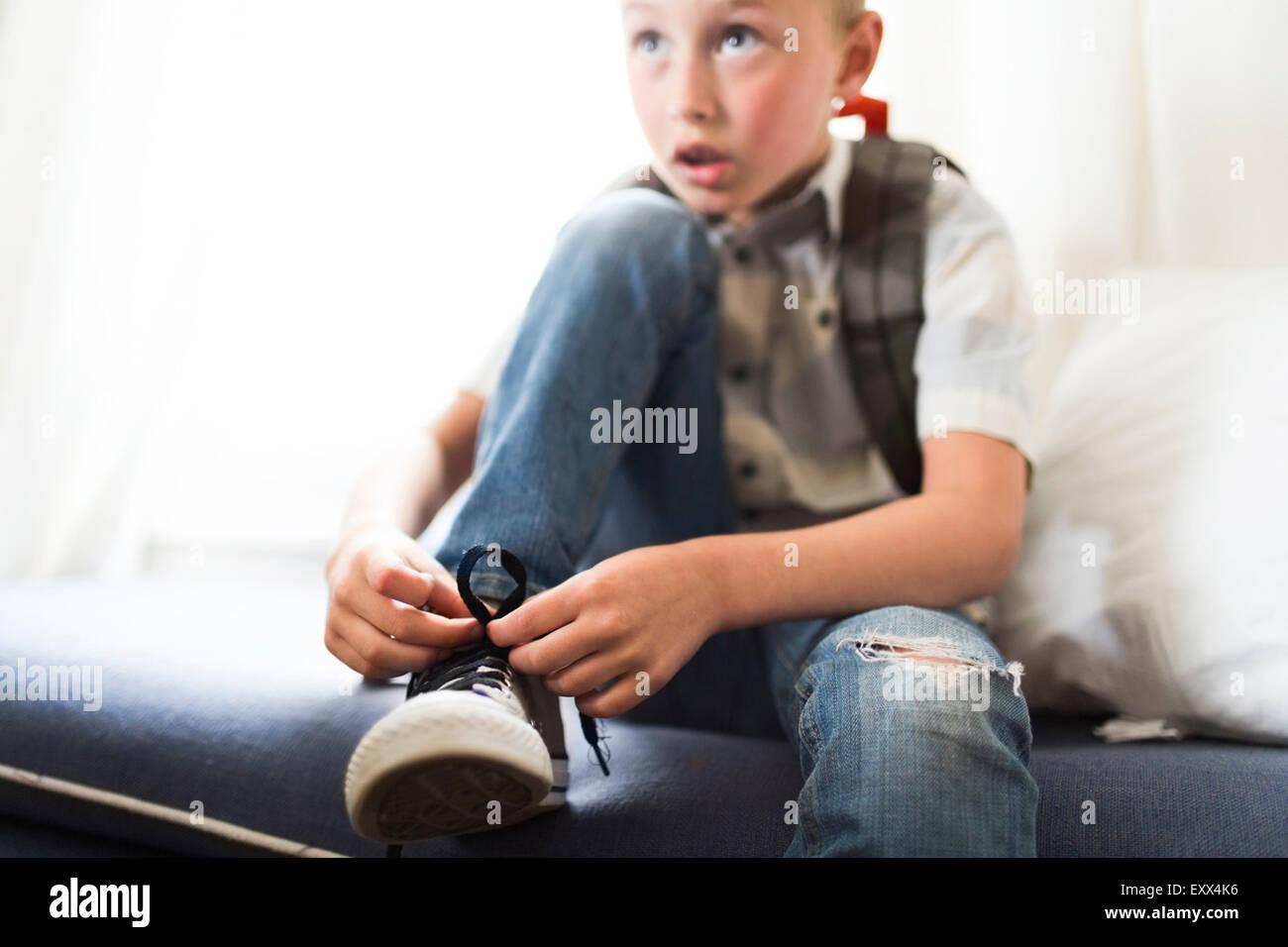 Boy (6-7) atar los zapatos Imagen De Stock