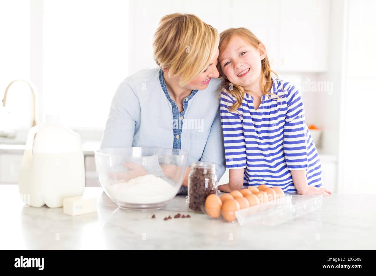 Retrato de niña (4-5) pasar tiempo con mamá en la cocina Imagen De Stock