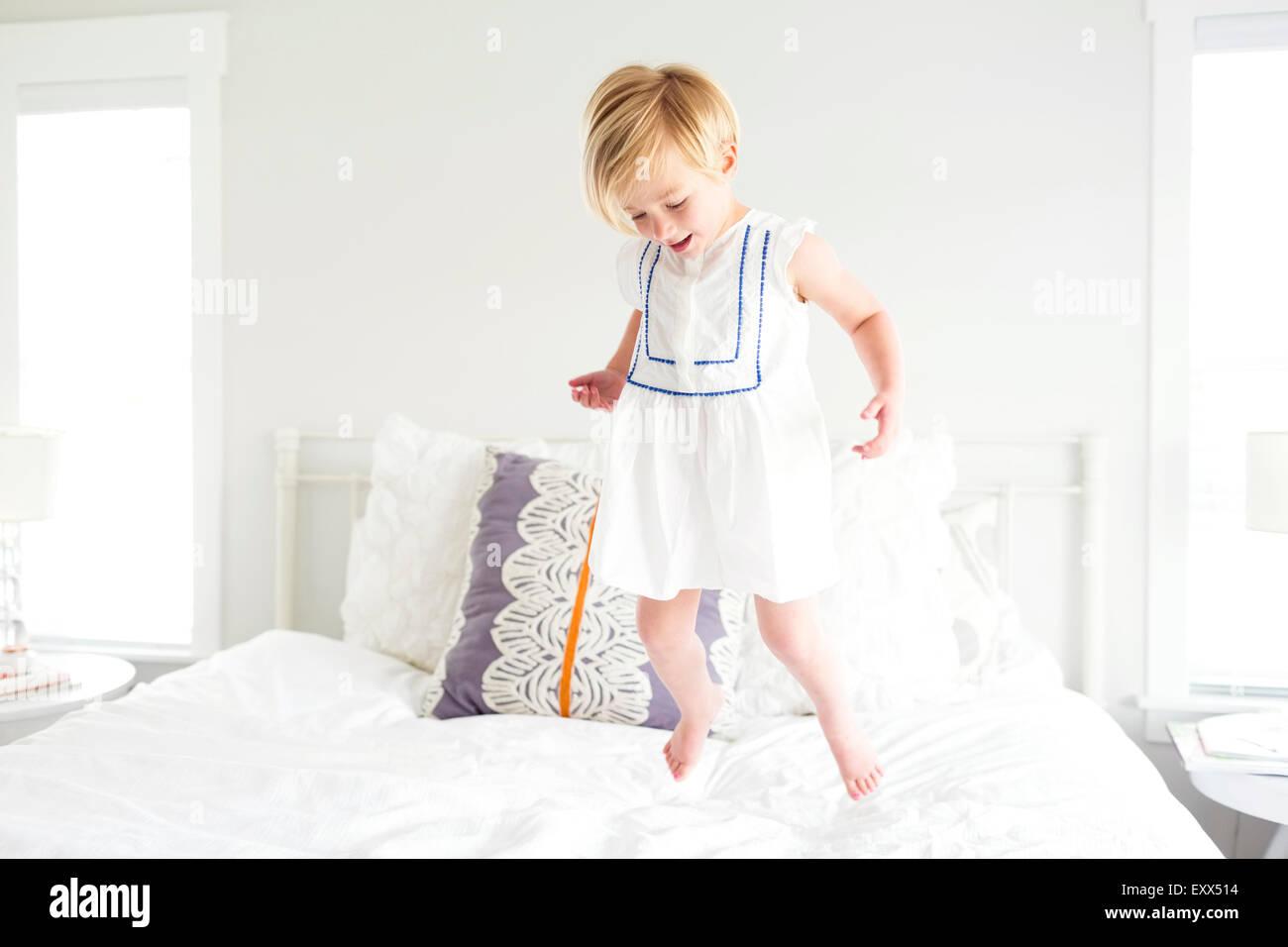 Chica (2-3) saltar en la cama Imagen De Stock