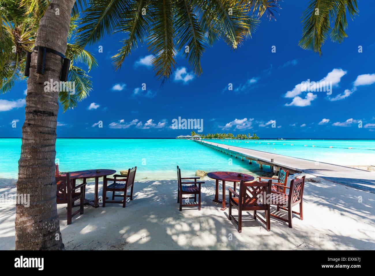 Mesas y sillas en la sombra de la palmera en la increíble isla tropical Imagen De Stock