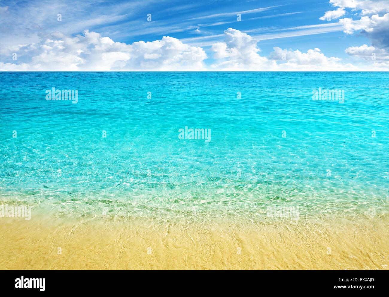 Fondo de verano en la playa, agua clara y azul cielo nublado. Imagen De Stock