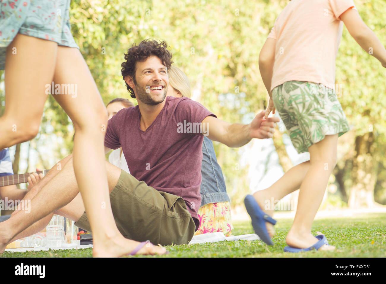 Hombre en picnic viendo los niños juegan Imagen De Stock