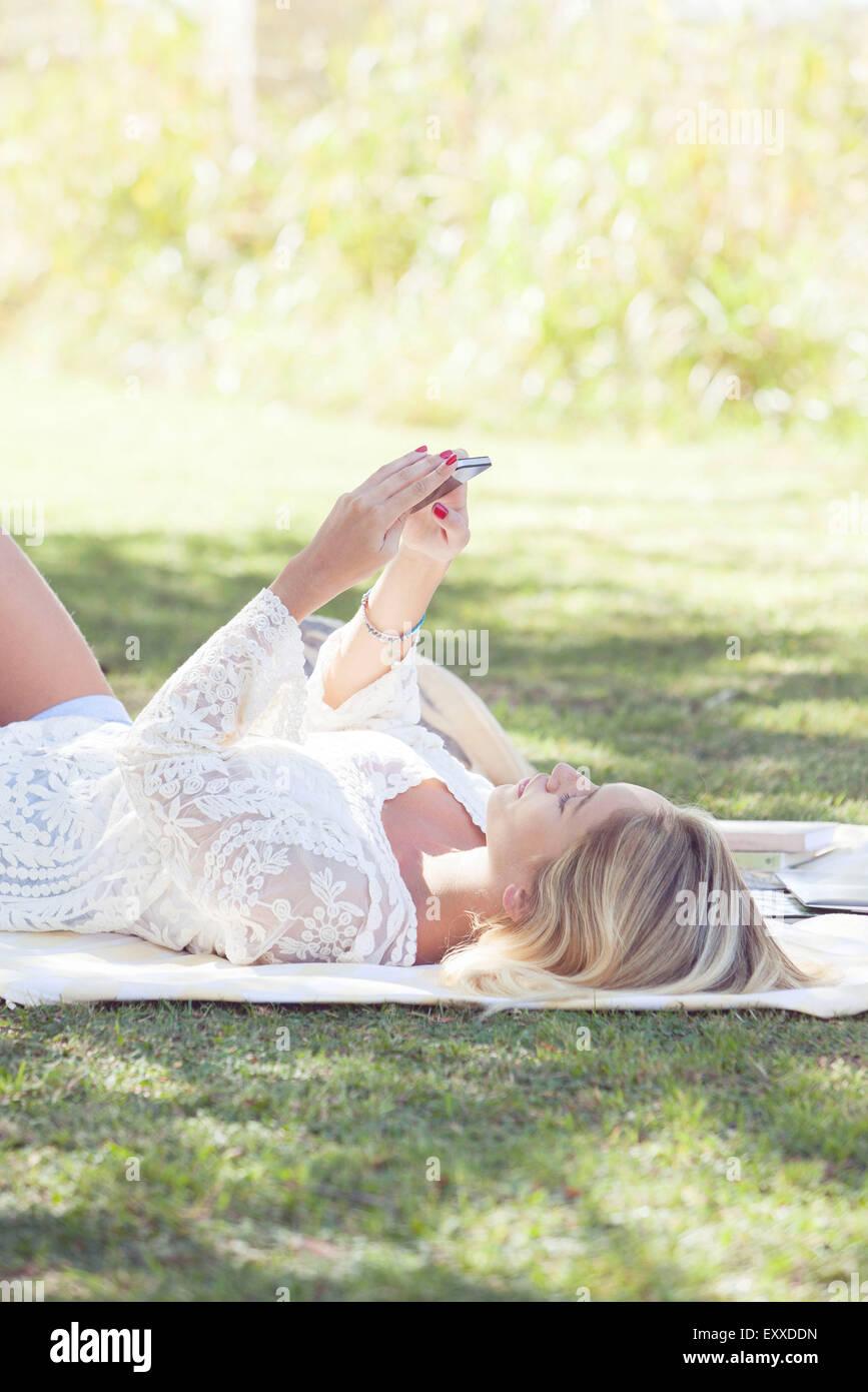 Mujer relajante en el parque con el smartphone Imagen De Stock