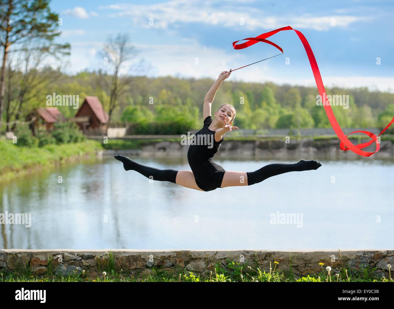 Joven gimnasta muestra Split Jump Imagen De Stock