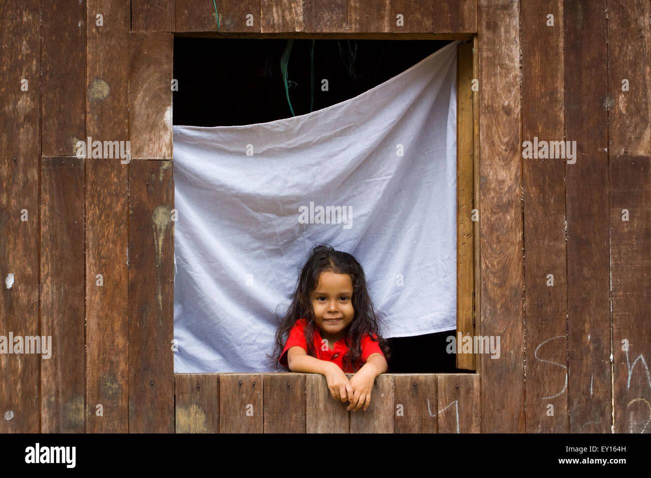 Cute Little Girl en la ventana de su casa de madera sonriendo ante la cámara en el Castillo, Nicaragua Foto de stock
