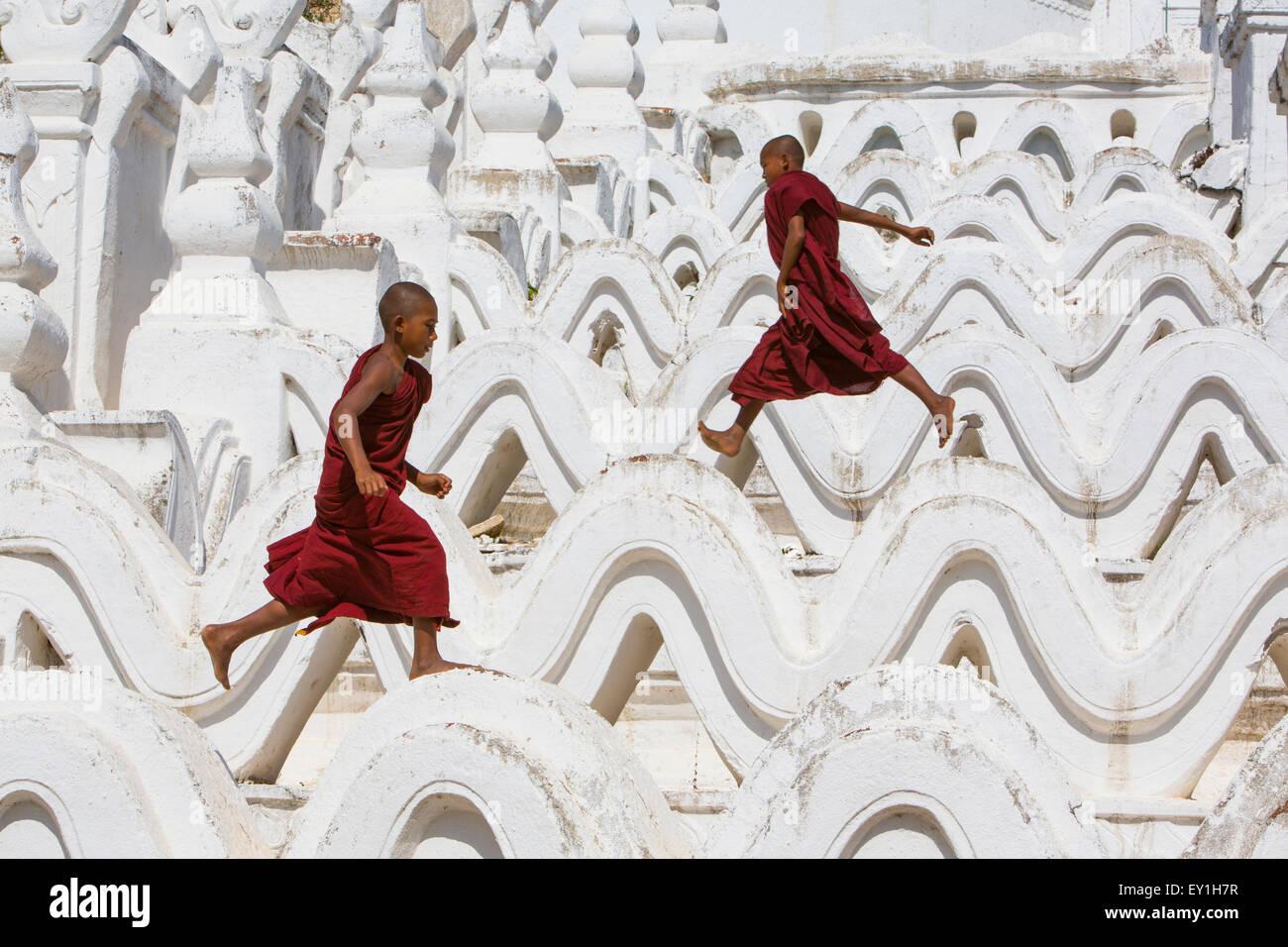 Los monjes novicios túnicas rojas saltando olas en Hsinbyume Paya templo, Mandalay, Myanmar Foto de stock