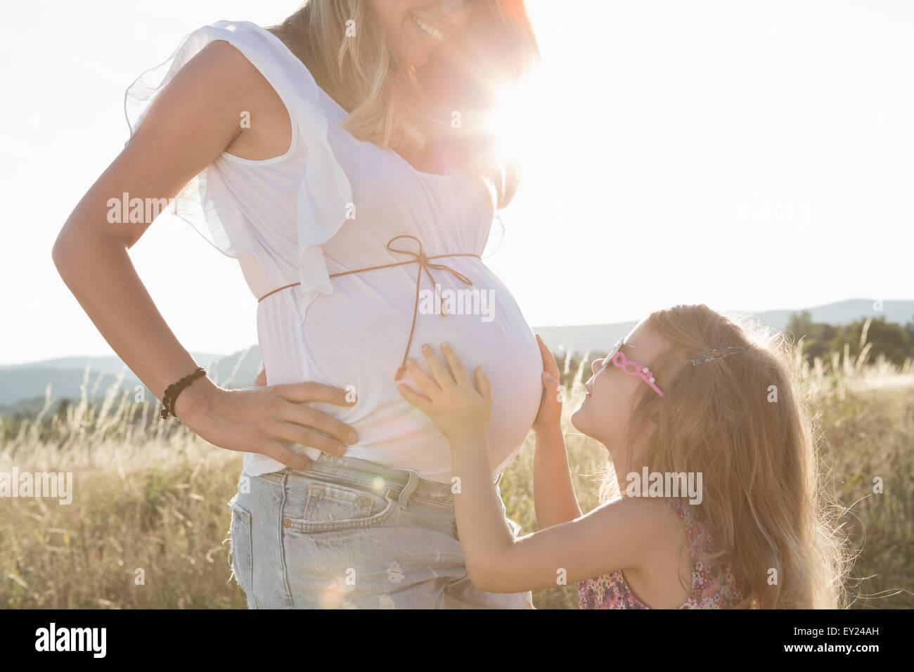 Chica tocando las madres embarazadas en campo de estómago Foto de stock