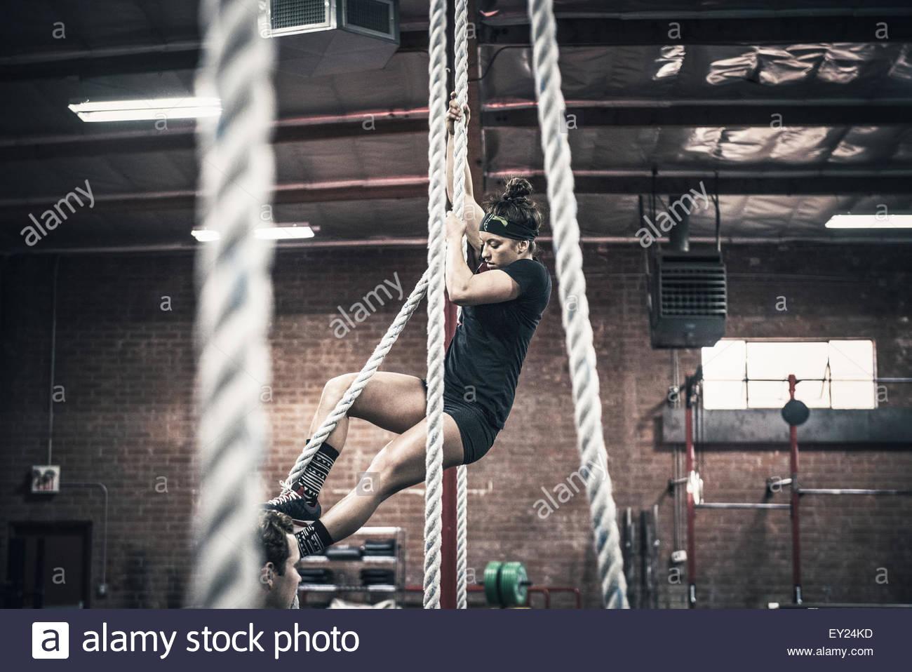 Mujer joven tipo cuerda de escalada en el gimnasio Imagen De Stock