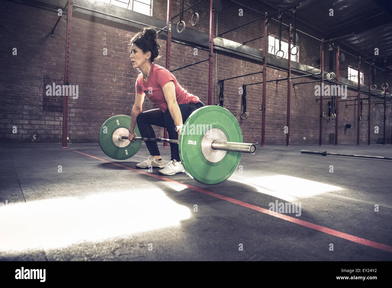 Mujer joven agacharse para levantar barbell en gimnasio Imagen De Stock
