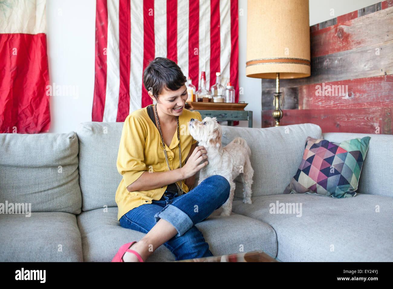 Mujer joven acariciar a perros en la sala de sofá Imagen De Stock