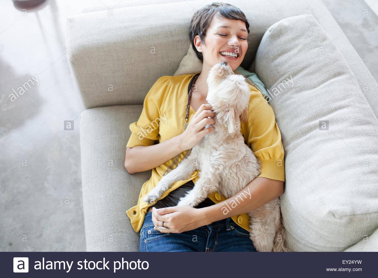 Mujer joven abrazando perro en la sala un sofá Imagen De Stock